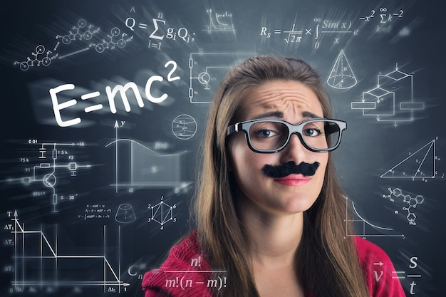 Tired girl is wearing glasses and fake mustaches over science background with formulas