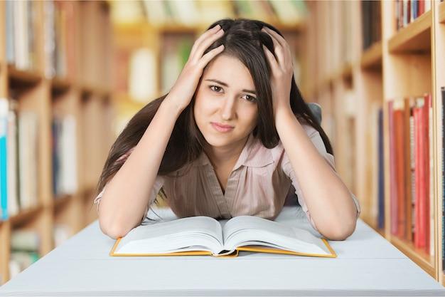 Усталая девушка читает трудную книгу в библиотеке