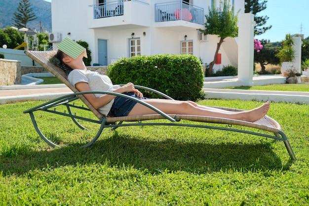 Усталая девушка спит с книгой на лице. девушка-подросток, лежа на садовом шезлонге на лужайке возле дома, солнечный летний день