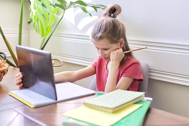 家で勉強している疲れた女子学生、デジタルタブレットを使用している子供。遠隔教育、オンラインレッスン、ビデオ会議、電子形式の学校レッスン。学校、技術、教育、子供の概念