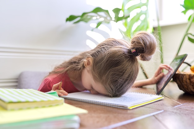 Tired girl student studying at home, girl in desperation laid her head on the table.