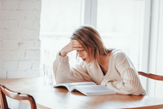 Tired girl in white sweater with book at kitchen