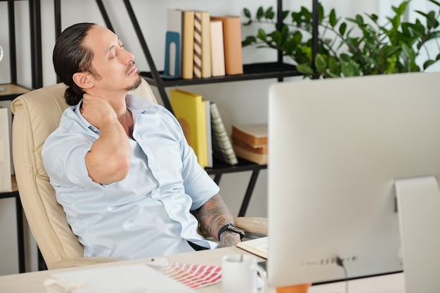 Tired graphic designer feels fatigue massaging tensed muscles of stiff neck trying to relieve pain after sedentary computer work in incorrect posture or uncomfortable office chair..