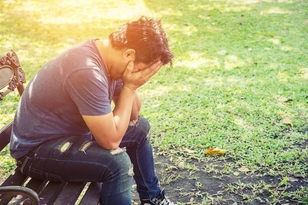 그의 손으로 그의 얼굴을 덮고 피곤 된 남자