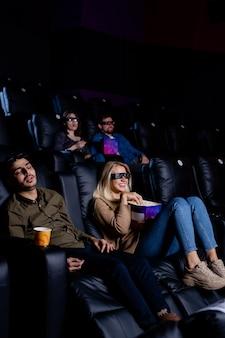映画館の肘掛け椅子で寝ている疲れた男、ポップコーンを持って映画を楽しんでいる3d眼鏡のガールフレンド