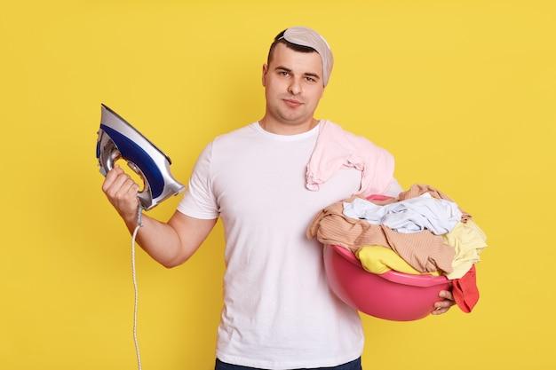 家事をしている疲れたハンサムな男は、衣類にアイロンをかける準備ができており、きれいな衣類でいっぱいの洗面器を持っており、アイロンがけが必要で、黄色い壁の上に孤立してポーズをとっています。