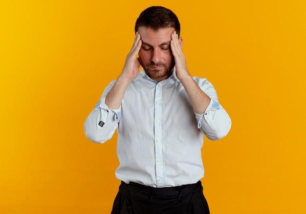 Uomo bello stanco tiene la testa guardando in basso isolato sulla parete arancione
