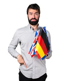 Усталый красивый мужчина с бородой, держащий много флагов