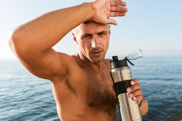 額を拭く疲れたハンサムな上半身裸のスポーツマン