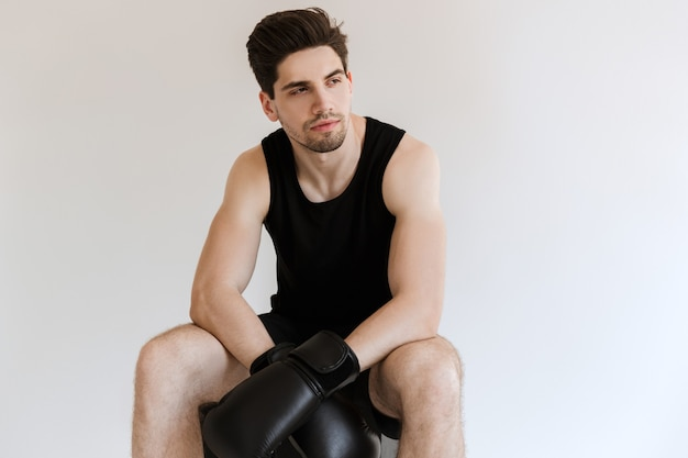 Tired handsome strong young sports man boxer in gloves sitting and have a rest isolated.