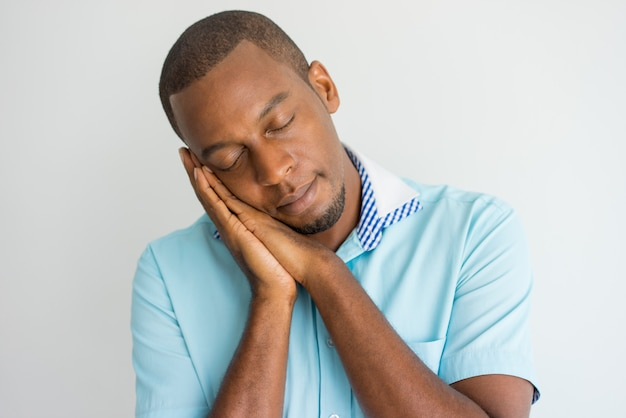 Tired handsome young african man with closed eyes pretending that he sleeping.