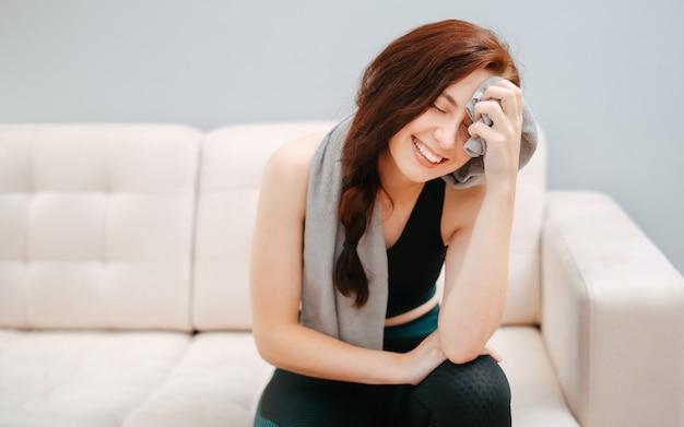 집에서 운동한 후 얼굴에 수건을 두른 피곤한 행복한 여성