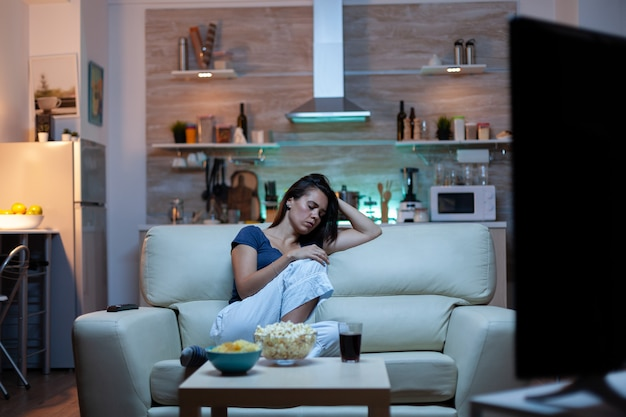 Tired housewife falling asleep in front of tv sitting on cozy couch in living room. exhausted lonely sleepy bored woman in pajamas sleeping on sofa while watching television home alone late at night