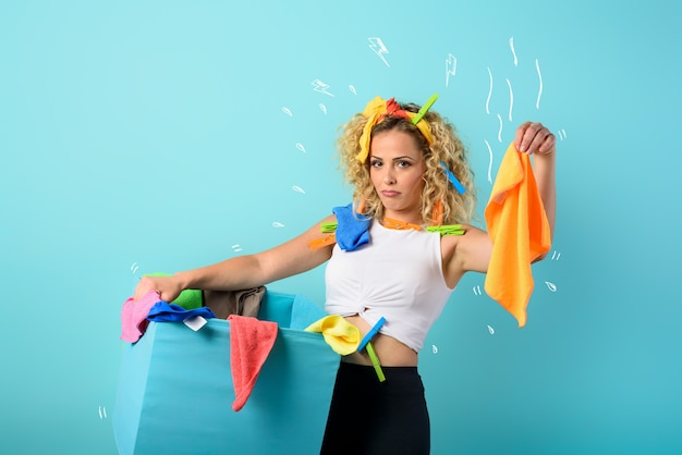 Tired housewife full of clothes and cloths to clean. cyan background