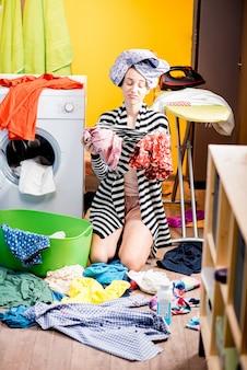 Усталая домохозяйка держит одежду, сидя на полу возле стиральной машины дома