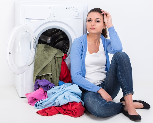 Tired housewife is doing laundry with washing machine.