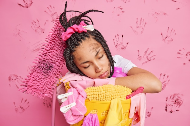 Tired housewife leans on laundry basket fall asleep after busy day has exhausted look dirty face dreadlocks poses near cleaning equipment isolated over pink wall