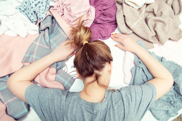 疲れた主婦は洗濯物の山に絶望して横たわっています。家庭の日常、日常生活。
