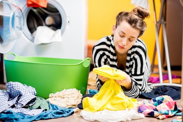 Усталая домохозяйка смотрит на одежду, сидя на полу возле стиральной машины дома