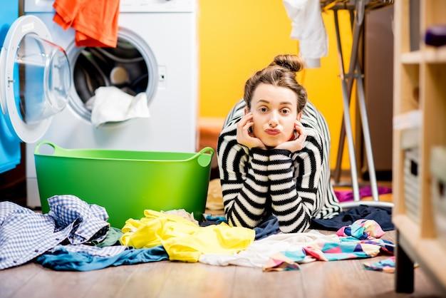 Усталая домохозяйка лежит на полу с кучей одежды возле стиральной машины дома