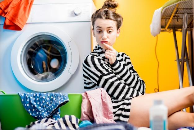 Усталая домохозяйка сидит возле стиральной машины с яркой одеждой дома
