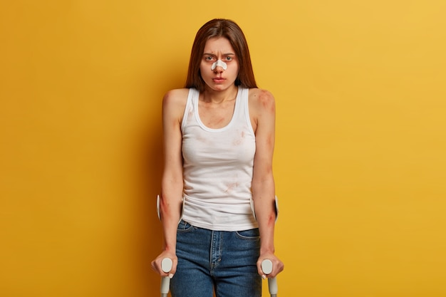 Tired hurt woman got trauma, being injured after recovery, has surgery rehabilitation, bleeding nose, spends time at home on sick leave, disabled to walk, isolated on yellow wall. limited abilities