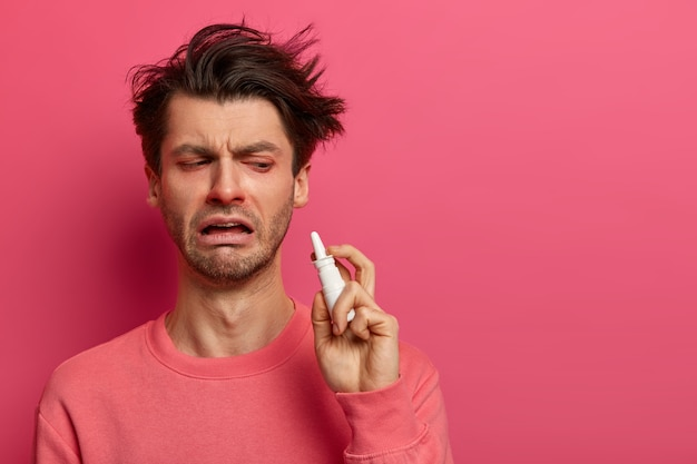 Tired ill man has symptomes of cold, holds nasal spray, wants to recover quickly, uses effective medicine, drips nose, getting worse, isolated on pink wall, feels bad. treatment of flu