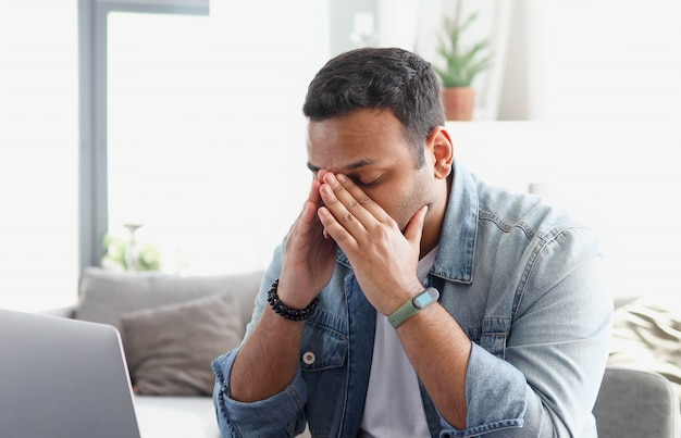 Tired indian young man feel eye strain from computer sitting at the desk in the office, sedentary lifestyle, man on the verge of emotional stress from overwork at work