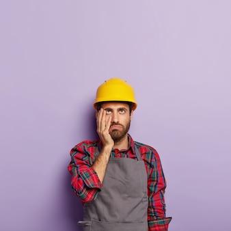 피곤한 산업 노동자가 노란색 안전모와 앞치마를 입는다.