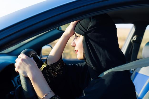 ハンドルの後ろに座っている交通渋滞で疲れたイスラムの女性