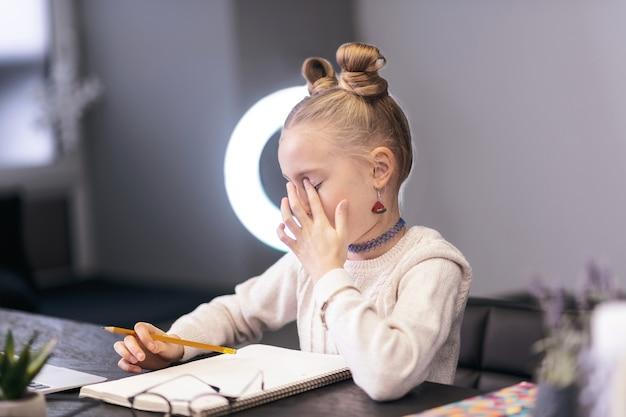 疲れた子供。テーブルに座っている間疲れを感じる白いセーターを着ているかわいい青い目の長い髪の少女
