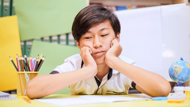 Tired little asian boy resting his head on his arms at his desk looking bored while doing homework.