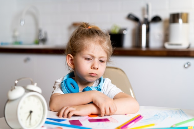 Tired little blonde girl at home at the kitchen table the concept of home education