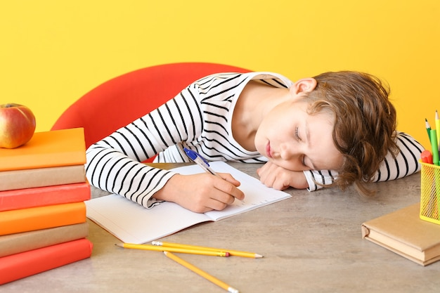Tired little boy sleeping at table instead of doing homework