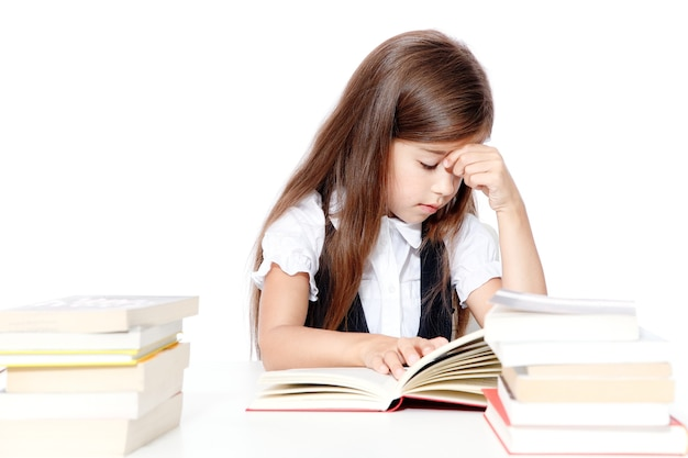 Tired little child girl sleeping on the desk at school.