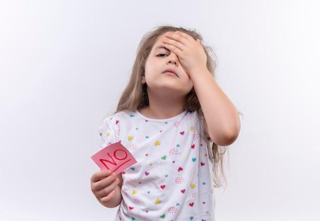 La piccola ragazza stanca della scuola che porta il contrassegno di carta della tenuta della maglietta bianca mise la mano sulla fronte sulla parete bianca isolata