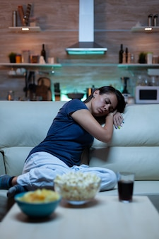 Tired lonely woman sleeping on sofa in living room while watching film