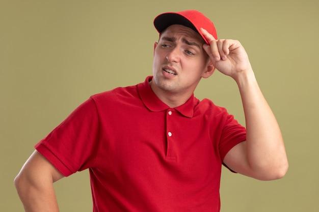 올리브 녹색 벽에 고립 된 모자를 들고 유니폼과 모자를 쓰고 측면 젊은 배달 남자를보고 피곤