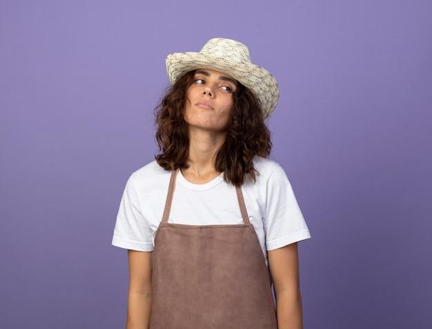 Stanco guardando lato giovane giardiniere femminile in uniforme che indossa il cappello da giardinaggio