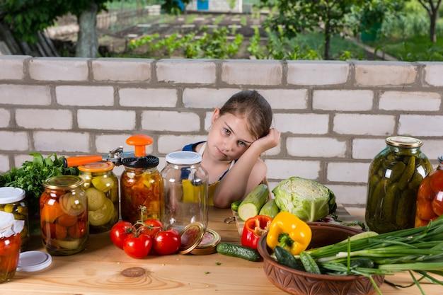 手に寄りかかって退屈そうに見える疲れた表情の少女は、新鮮な野菜と漬物の瓶で覆われたテーブルに座って、屋外の庭に保存します