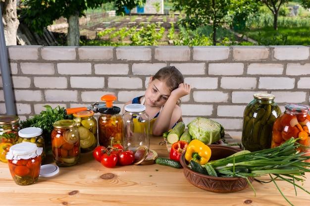 手に寄りかかって、新鮮な野菜と漬物の瓶で覆われたテーブルに座って、庭の屋外で疲れているように見える若い女の子