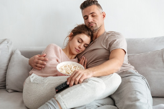 Tired loving couple sitting on couch together with popcorn and having rest at home