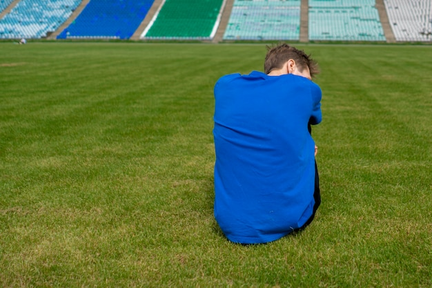 Усталый спортсмен-спортсмен расслабляется на траве после тренировок