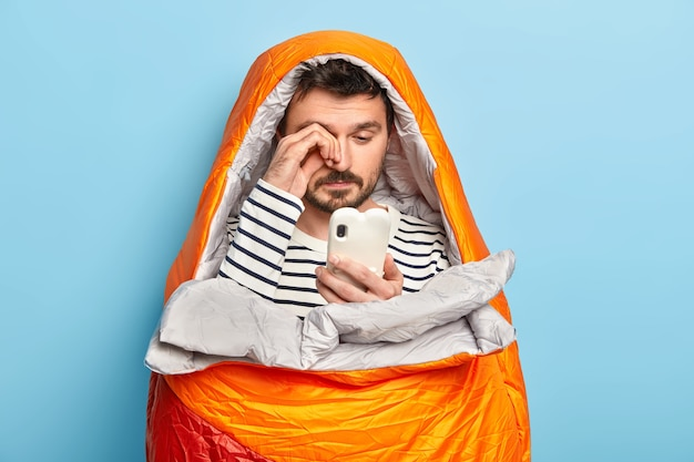 Tired male camper rubs eyes, uses mobile phone, tries to connect to intenrnet in wild nature, poses in sleeping bag, has all necessary equipment needed for camping