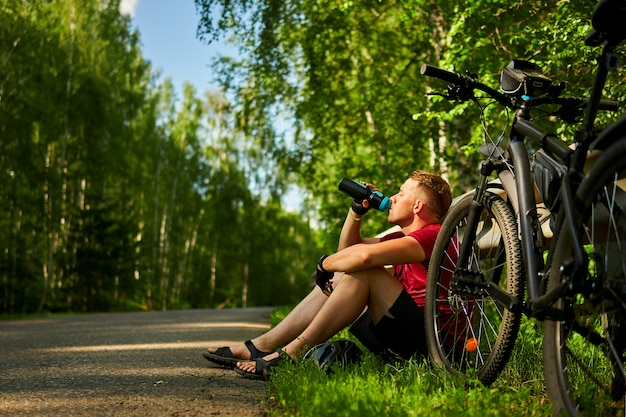 Tired male cyclist sits on the side of the road and drinks water from a bottle.