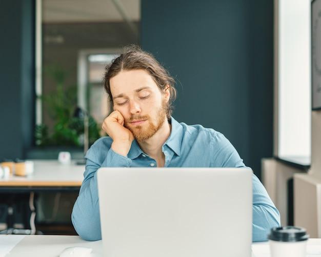 仕事で眠りに落ちる疲れた男性サラリーマン