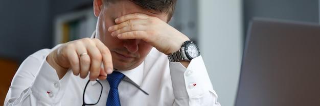 Утомленный мужской работник офиса сидя на отдыхать таблицы. тело не может функционировать без полноценного отдыха, питания и физической активности. круглосуточная и безостановочная работа перед финальным проектом
