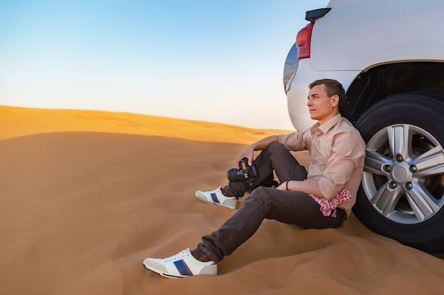Усталый фотограф-мужчина сидит на собачке возле разбитой машины