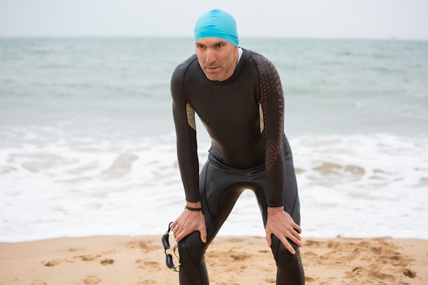 Tired male swimmer standing on beach