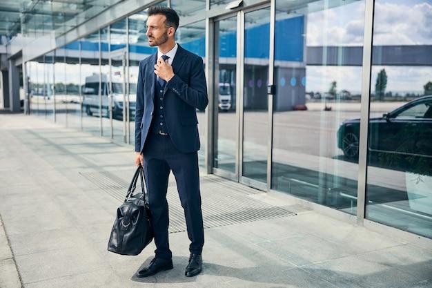 上品なスーツを着た疲れた男性旅行者が空港に到着するとネクタイを固定し、バッグを持っています